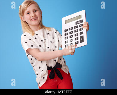 happy modern child in red pants сlicking on the button on the calculator on blue background - Stock Photo