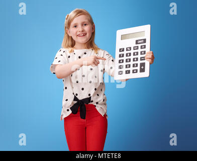 happy modern child in red pants pointing at calculator isolated on blue - Stock Photo