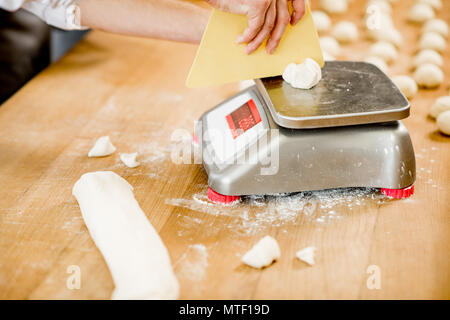 Baker weighing dough portions for baking buns at the manufacturig, close-up view - Stock Photo