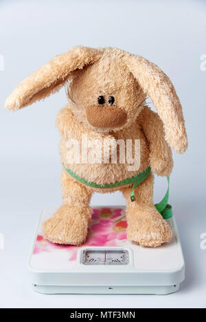 A soft toy rabbit with a centimeter ribbon stands on the scales. - Stock Photo