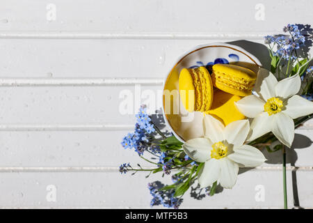 Colorful macaroons and flowers on white wooden table. Sweet macarons. Top view with copy space for your text.Tasty dessert flat lay and daffodils and forget-me-not flowers. - Stock Photo