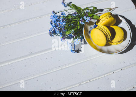 Macaroni tasty French dessert on white wooden table.macarons on vintage background. Macaron is sweet. Toned image. Copy space. tasty yellow French Macarons and forget-me-not flowers - Stock Photo