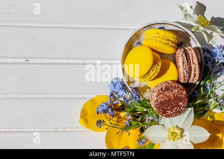 Flowers, macarons in pastel color on the white wooden background, top view. Copy space.chocolate macaroon and lemon dessert isolated. - Stock Photo