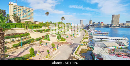 CAIRO, EGYPT - DECEMBER 24, 2017: The riverside promenade on Gezira island with cozy ornamental garden, pleasure boats in tourist port and picturesque - Stock Photo