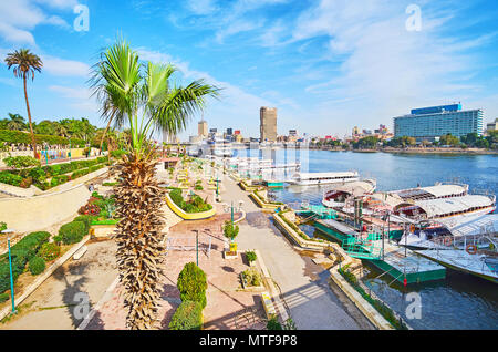 The scenic ornamental garden on the bank of Nile river with a view on boats, Downtown district and 6th of October bridge behind the tall palm tree, Ge - Stock Photo