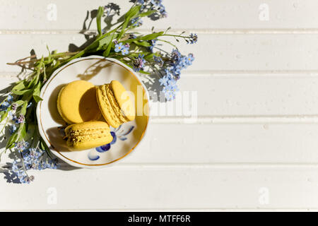 delicious colorful macaroons on trendy vintage wooden table with forget-me-not flowers and confetti, flat lay. tasty yellow, lemon macaroons. space for text. candy for party. Toned image