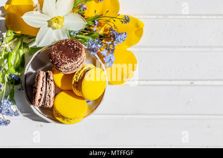 macarons or macaroons dessert sweet beautiful to eat. chocolate and lemon desserts on a white wooden table.Tasty dessert flat lay and daffodils and forget-me-not flowers. - Stock Photo