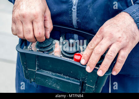 Remote control for concrete pump truck in operator hands at construction site. Vintage style. - Stock Photo