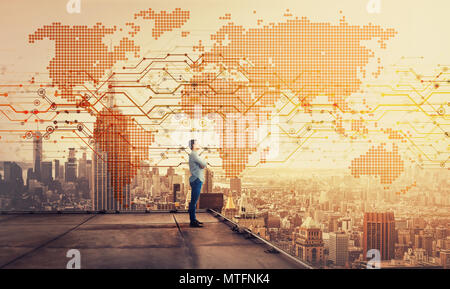 Side view of a thoughtful businessman standing on the rooftop of a skyscraper looking over the big city at sunset with a world map hologram projection - Stock Photo