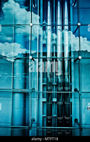 clouds reflected in a glass wall behind which are modern industrial tubes and pipes - Stock Photo
