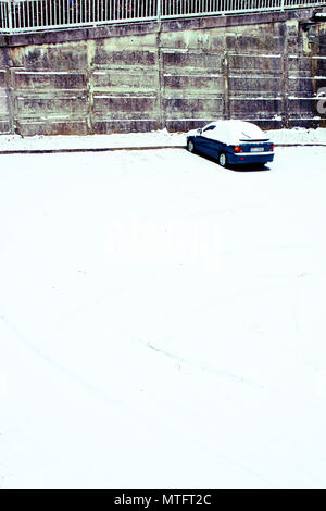 a blue car lonely parked in a parking lot in winter under snow - Stock Photo