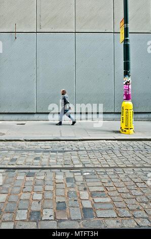 bearded adult man walking along a sidewalk, alone - Stock Photo