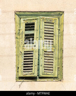 Cyprus, Larnaca. Green weathered window on a yellow wall in the old city - Stock Photo