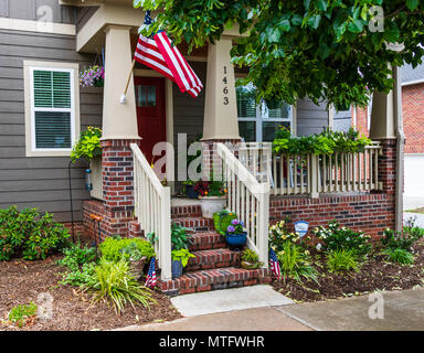 HICKORY, NC, USA-27 MAY 18:  A colorful house front, with green, blue, orange, and red.  A small American flag on either side of steps, and a larger o - Stock Photo