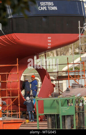 Red ship in dry dock through a fence, Capetown Harbour, Capetown, South Africa - Stock Photo