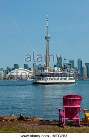 Muskoka chair Toronto Island ferry and Toronto skyline cityscape from Toronto Island Park Toronto Ontario Canada - Stock Photo