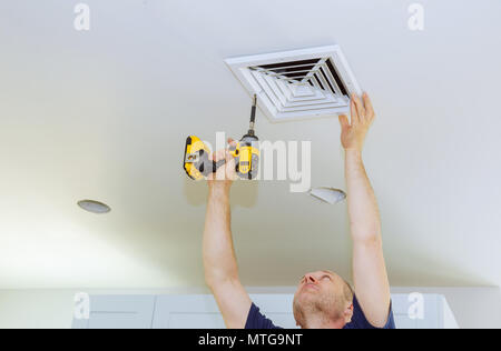 Man installing of HVAC, heating ventilating and cooling after replacing the air filter. Vent on the wall - Stock Photo