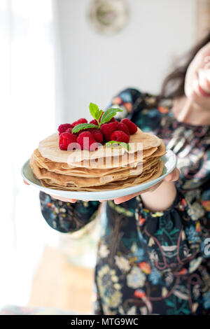 Photo of happy young woman standing at the kitchen in home cooking. Focus on pancakes. Copy space - Stock Photo