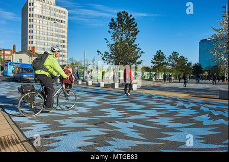 A man in yellow hi vis jacket cycling across the new lighting blue crossing point outside Coventry station - Stock Photo