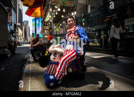 NEW YORK, NY/USA - APRIL 2017: Street performer taking a break nearby Times Square - Stock Photo