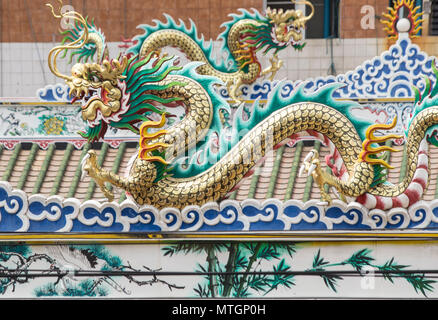 BANGKOK/THAILAND - JUNE 2017: Detail of a dragon on a ornate roof top in Silom district - Stock Photo