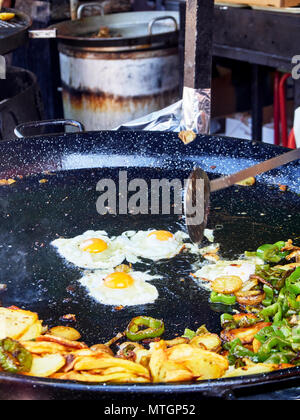Spanish eggs in progress. Fried eggs with potatoes and peppers to the frying pan. Spanish street food. - Stock Photo