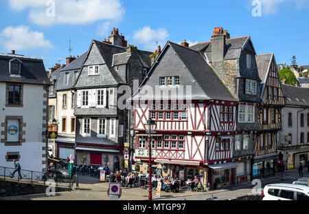 Within a half-timbered building on a busy corner, a lively cafe full of people in Morlaix, Brittany, France. - Stock Photo