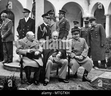 British Prime Minister Winston Churchill, U.S. President Franklin Roosevelt, and Soviet leader Joseph Stalin met at Yalta in February 1945 to discuss their joint occupation of Germany and plans for postwar Europe. Behind them stand, from the left, Field Marshal Sir Alan Brooke, Fleet Admiral Ernest King, Fleet Admiral William D. Leahy, General of the Army George Marshall, Major General Laurence S. Kuter, General Aleksei Antonov, Vice Admiral Stepan Kucherov, and Admiral of the Fleet Nikolay Kuznetsov. February 1945. - Stock Photo