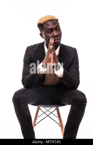 Serious African man in business formal outfit sitting on the chair isolated on white - Stock Photo