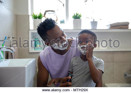 Father and son playing with shaving cream in the bathroom - Stock Photo