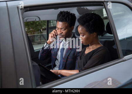 Business man and woman sitting in the back seat of car - Stock Photo