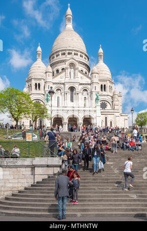 Tourist flock to visit the Sacre-Coeur Basicica in the Montmartre area of Paris France. - Stock Photo