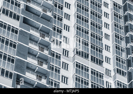 Exterior of the new apartment building under construction on sunny day. - Stock Photo