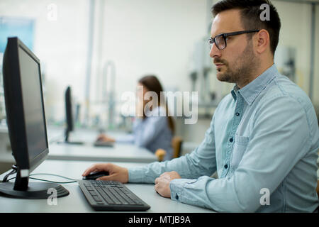 Side view of focused students using desktop pc in classroom at Technical faculty - Stock Photo