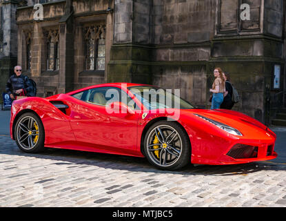 People look enviously at a bright red Ferrari 488 GTB coupe sports car, parked on cobbled street, Royal Mile, Edinburgh, Scotland, UK - Stock Photo