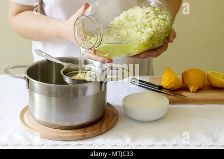 Elder flowers, water, lemon and sugar, ingredients and a woman preparing an elderberry syrup. Rustic style, selective focus. - Stock Photo