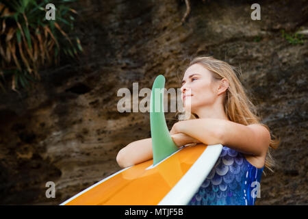 Sporty girl in bikini with surfboard stand by black cliff on beach. Surfer woman look at sea surf and breaking waves. Active people in sport adventure - Stock Photo
