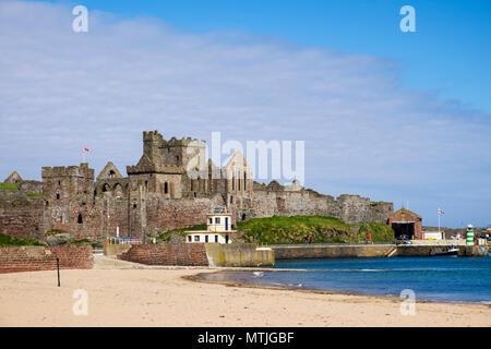 Peel castle ruins and sandy beach in Peel Bay. Peel, Isle of Man, British Isles - Stock Photo