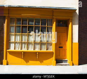 The front of a Victorian house painted in yellow in Bermondsey Street, London, UK - Stock Photo