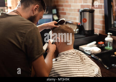 Barber and bearded man in barber shop - Stock Photo