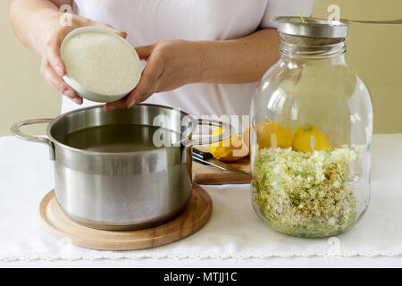Elder flowers, water, lemon and sugar, ingredients and a woman preparing an elderberry syrup. Rustic style. - Stock Photo