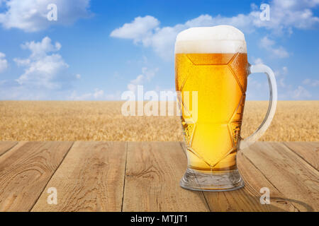 mug of light beer with foam and bubbles on wooden table against ripe wheat field on summer day - Stock Photo