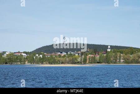 City of Kuopio in Eastern Finland at the shores of Lake Kallavesi, in front of Puijo mountain with its scenery tower and ski-jump tower sticking up. - Stock Photo