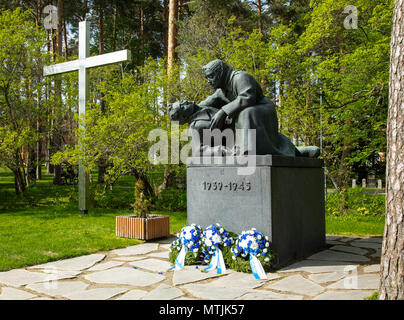 The monument of the fallen in Finland's wars at the cemetery of Kuopio, with wreaths of the Memorial Day placed in front of the sculpture. - Stock Photo