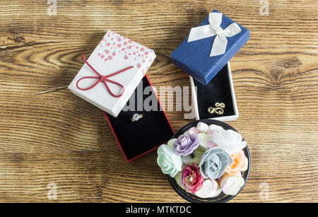 Golden rings lie in a red and blue boxes with many button roses on wooden table - Stock Photo