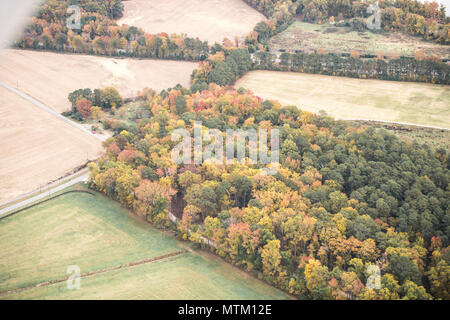 Flying in a Cessna Aerobat over Virginia fields, farmland and forest in the colorful fall. Autumn leaves on great display in aerial photography view. - Stock Photo
