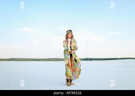 Young woman wearing green beach robe and black swimsuit standing - Stock Photo