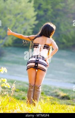 Pretty female teenager view from rear behind back extended finger and hand  hitchhiking on countryside road - Stock Photo