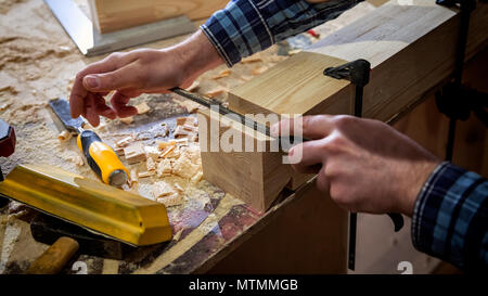 Close up experienced carpenter in work clothes and small buiness owner working in woodwork workshop,  using chisel for cutting out of wood  in worksho - Stock Photo