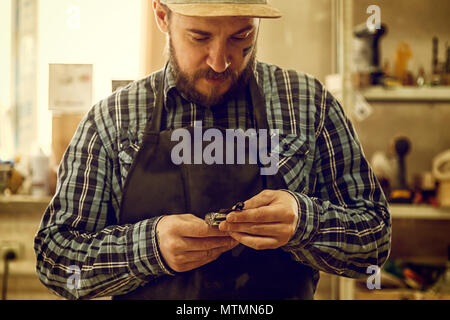 Close up of a experienced carpenter in work clothes and small buiness owner working in woodwork workshop - Stock Photo